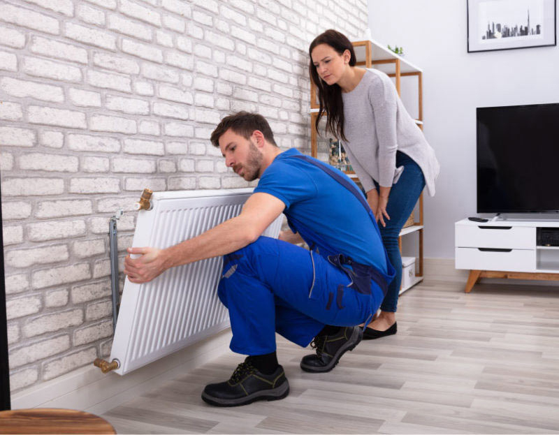 A Mulgas engineer carefully installing a new radiator in the living room of a modern West Molesey home