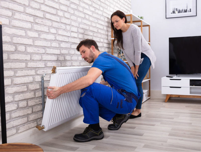 A Mulgas engineer installing a new radiator in a modern home in Wimbledon as part of a central heating installation