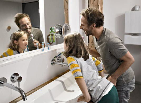 father and daughter brushing their teeth in their warm bathroom after the Mulgas team repaired their boiler in Richmond