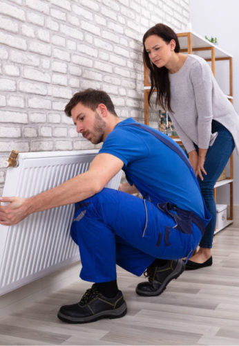 A Mulgas 'Gas Safe' certified engineer installing a radiator in a modern home in Richmond while the happy customer watches
