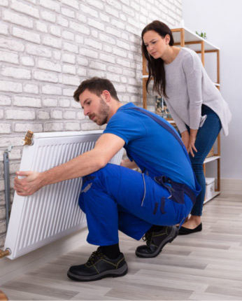 A Mulgas engineer installing a new radiator in the living room of a house in Shepperton while the customer watches